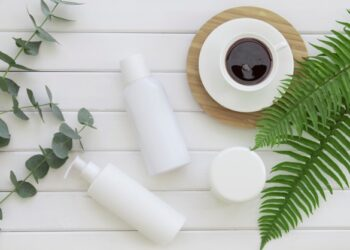 Skin cream bottles over wood background with tropical fern and eucalyptus